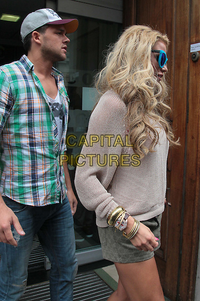 Leandro Penna & Katie Price (Jordan) at BBC Radio 1 and Kiss FM, London, England..July 20th, 2011.half length jeans denim green check shirt baseball cap hat sunglasses shades beige top green khaki shorts side profile bracelets couple.CAP/HIL.©John Hillcoat/Capital Pictures .