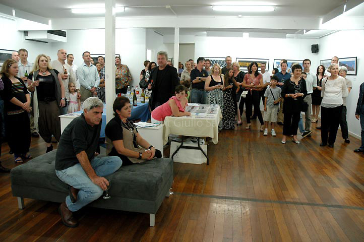 Some of the crowd at the opening night listen to Earle Bridger (not in shot) speak as he opens the exhibition.