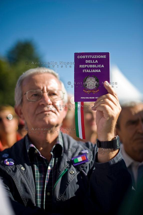 """Un partecipante alla manifestazione """"Ricucire l'Italia"""" organizzata a Milano da Libertà e Giustizia, mostra una copia della costituzione Italiana"""