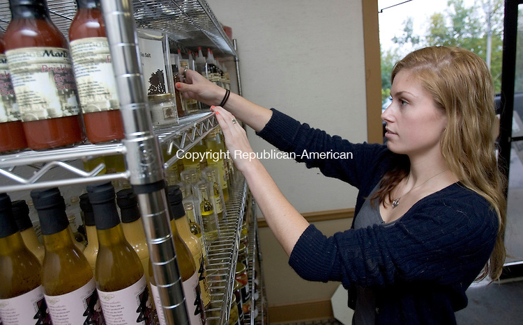 WATERBURY, CT. 28 September 2012-092812SV06-Erin Sullivan of The Olive Oil Factory sets up a display at a temporary location in Volubilis Foods at 407 Brookside Road in Waterbury Friday.  While the cleanup continues on Huntington Avenue, the factory is expected to resume production next week at Volubilis Foods on Brookside Road. The factory building and inventory were greatly damaged after a water main break just outside the building. .Steven Valenti Republican-American