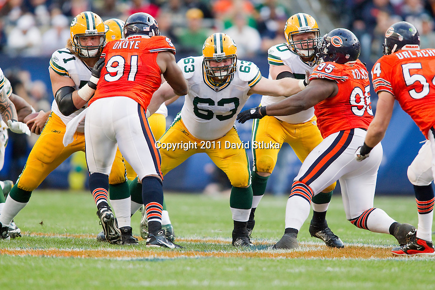 Green Bay Packers offensive linemen Josh Sitton (71), Scott Wells (63) and T.J. Lang (70) block against the defensive linemen of the Chicago Bears during a week 3 NFL football game on September 25, 2011 in Chicago. The Packers won 27-17. (AP Photo/David Stluka)