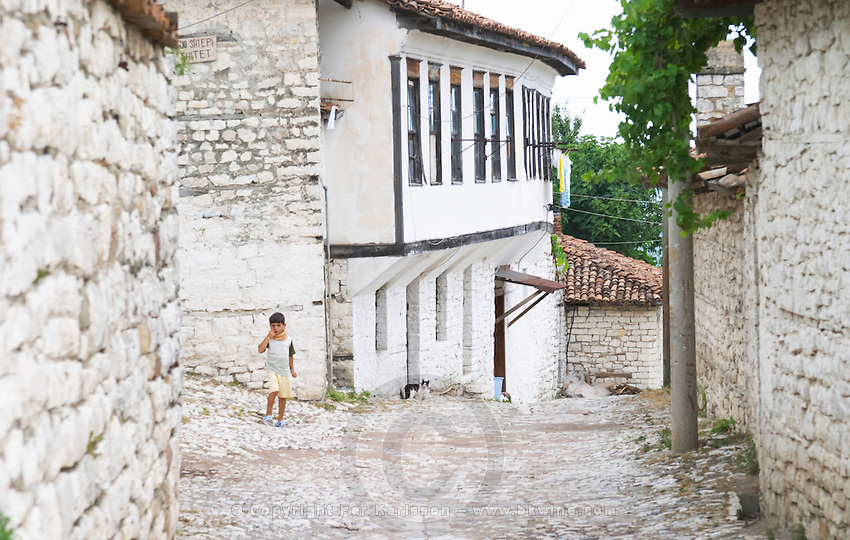 Traditional ottoman white stone houses, a young boy child walking on the cobble stone street. Berat upper citadel old walled city. Albania, Balkan, Europe.