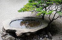A stone basin reflects a beautifully manicured shrub at a karesansui (dry landscape) garden in Ritsurin Koen, Takamatsu.