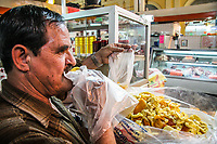 Pablo Davila del la fruteria Borbon empaca y prueba los llamados orejones de manzana y otros frutas