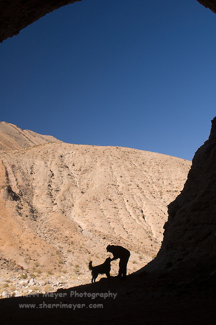 Man & dog at the entrance to a cave in Cottonwood Canyon, Death Valley National Park, California