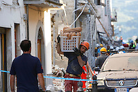 An operator carries bread among rubble of collapsed buildings in the village of Amatrice, central Italy, hit by a magnitude 6 earthquake at 3,36 am, 24 August 2016.<br /> Un operatore porta una cesta di pane sulle spalle, tra le macerie degli edifici crollati dopo il terremoto che alle 3,36 del mattino ha colpito Amatrice, 24 agosto 2016.<br /> UPDATE IMAGES PRESS/Riccardo De Luca