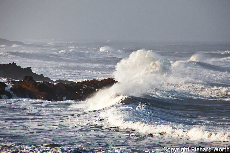 An incoming wave crashes into the rocks and blossoms into a water-cloud of white.