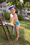My son, age two, dries off my chair after getting it wet with water from his wading pool. His hat is fresh from the pool.