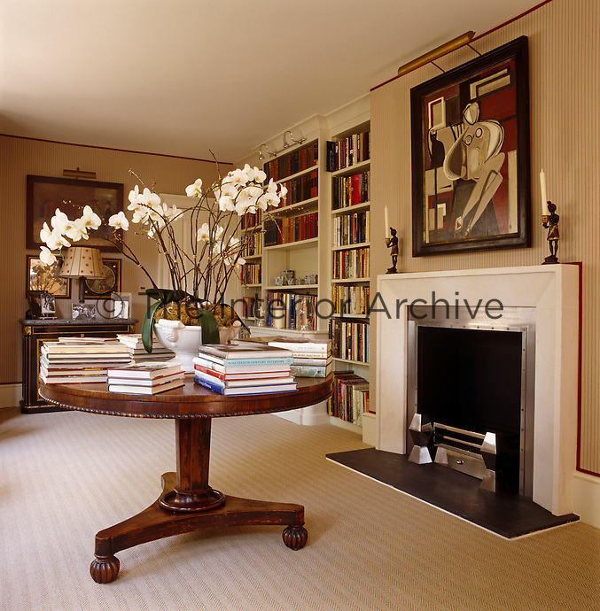 The dining table folds away and is replaced with a George IV circular pedestal table when the room reverts to a library