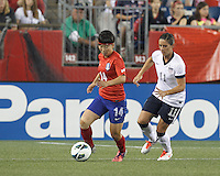 Korea Republic substitute midfielder Kwon Hahnul (14) dribbles as USWNT substitute defender Ali Krieger (11) closes. In an international friendly, the U.S. Women's National Team (USWNT) (white/blue) defeated Korea Republic (South Korea) (red/blue), 4-1, at Gillette Stadium on June 15, 2013.