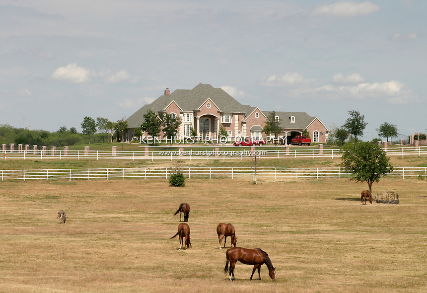 Sprawling modern estate in rural setting with obiligatory pick-up trucks in the driveway and horses in pasture in the foreground.