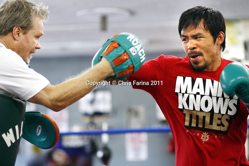 "April 4, 2011, Hollywood,Ca. ---  Superstar Manny Pacquiao(R) hits the mitts with his chief trainer Freddie Roach(L at the Wildcard Boxing Club in Hollywood Monday in preparation for his upcoming World Welterweight mega fight against ""Sugar"" Shane Mosley on Saturday, May 7 at the MGM Grand in Las Vegas.  Pacquiao vs Mosley is promoted by Top Rank in association with MP Promotions,Sugar Shane Mosley Promotions,Tecate and MGM Grand.  The Pacquiao vs Mosley telecast will be available live on SHOWTIME Pay Per View.  --- Photo Credit : Chris Farina - Top Rank  (no other credit allowed)  copyright 2011"