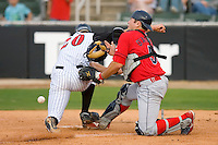 Jon Gilmore #20 of the Kannapolis Intimidators collides with catcher Travis D'Arnaud #5 of the Lakewood BlueClaws at Fieldcrest Cannon Stadium May 16, 2009 in Kannapolis, North Carolina. (Photo by Brian Westerholt / Four Seam Images)