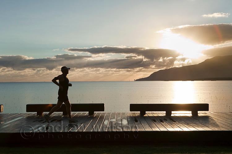 Jogger on the Esplanade boardwalk at dawn.  Cairns, Queensland, Australia