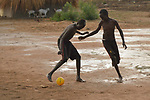 Boys play football in the Rhino Refugee Camp in northern Uganda. As of April 2017, the camp held almost 87,000 refugees from South Sudan, and more people were arriving daily. About 1.8 million people have fled South Sudan since civil war broke out there at the end of 2013. About 900,000 have sought refuge in Uganda.