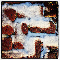The afternoon sun lights the dusting of snow on bricks in the 100 block of Duval Street in the Germantown section of Philadelphia on January 6, 2013.