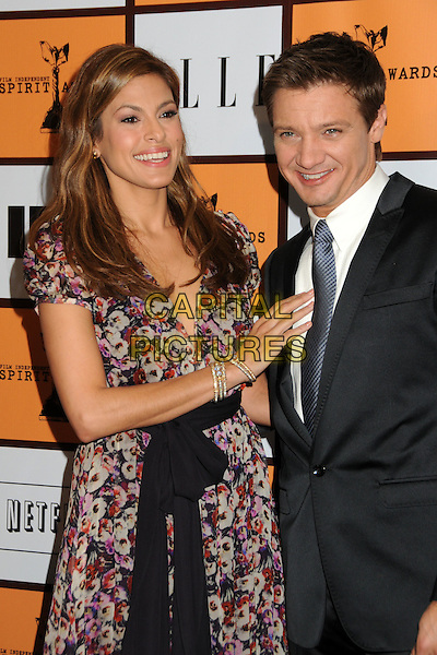 EVA MENDES & JEREMY RENNER .2011 Film Independent Spirit Award Nominations held at The London Hotel, West Hollywood, California, USA, .30th November 2010..half length black sash belt dress pink floral print smiling purple suit tie hand grey gray white shirt indie.CAP/ADM/BP.©Byron Purvis/AdMedia/Capital Pictures.