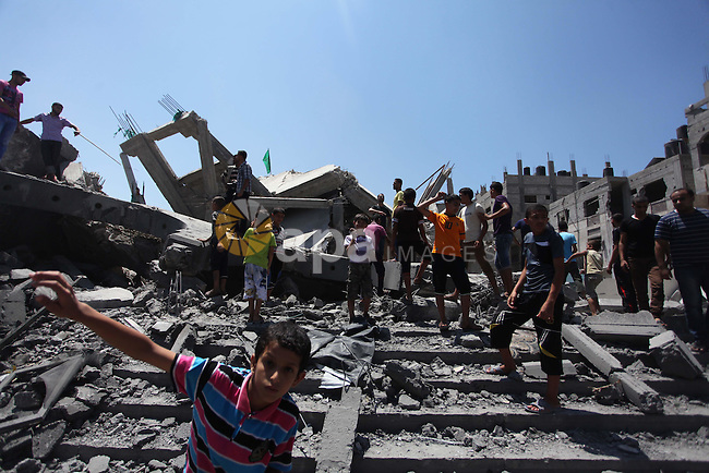 Palestinians inspect the remains of al-Shuhada mosque, which witnesses said was hit by an Israeli air strike, in Nuseirat refugee camp in the central Gaza Strip on August 10, 2014. Israel said on Sunday it was prepared for protracted military action in Gaza and would not return to Egyptian-mediated ceasefire talks as long as Palestinians kept up cross-border rocket and mortar fire. Israeli air strikes and shelling killed three Palestinians in Gaza on Sunday, including a boy of 14 and a woman, medics said, in a third day of renewed fighting that has jeopardised international efforts to end a more-than-month-old conflict. Photo by Ashraf Amra