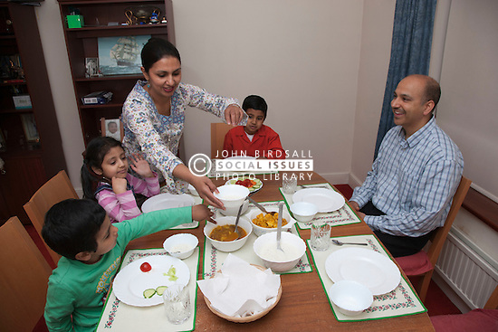 Asian family at dining room table, mother putting food out