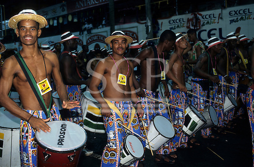 Salvador, Bahia, Brazil. Bloco Muzenza carnival block, drummers in colourful costumes.
