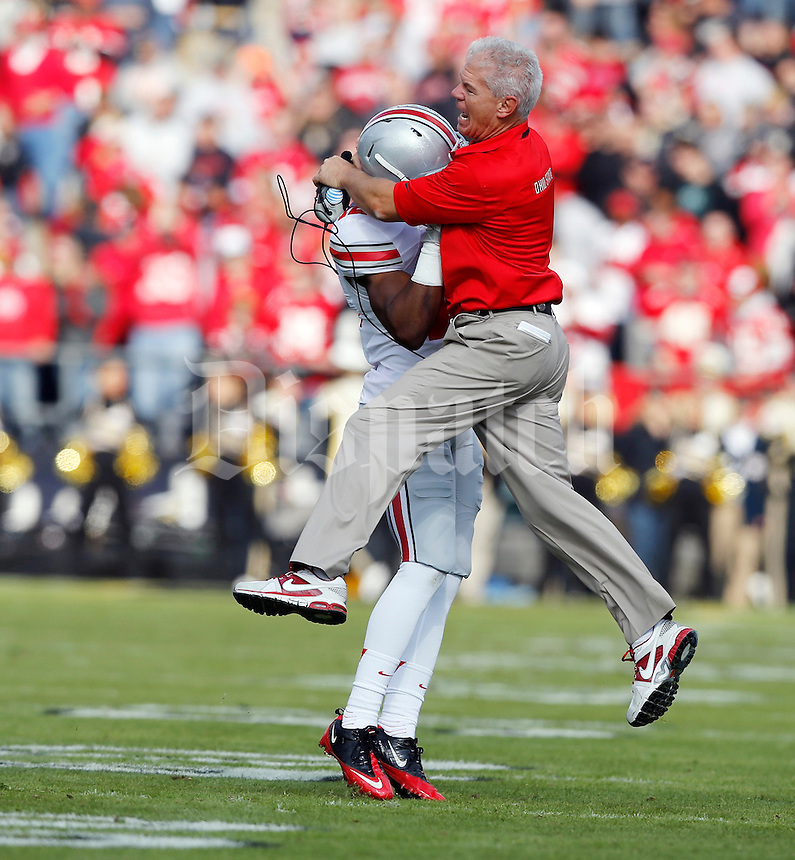 Ohio State cornerbacks coach Kerry Coombs leaps into cornerback Doran Grant (12) after Grant had a pick six interception during the first quarter of the NCAA football game at Ross-Ade Stadium in West Lafayette, Ind. on Nov. 2, 2013. (Adam Cairns / The Columbus Dispatch)