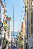 PORTUGAL, Lisbon, looking down a street in Barrio Alto area, Sea view in the background