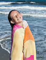 Cute young girl drying off with a beach towel.