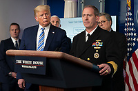 United States President Donald J. Trump, left, listens as Rear Admiral John P. Polowczyk, Vice Director, J4, Joint Staff speaks during a news briefing by members of the Coronavirus Task Force at the White House in Washington, DC on Monday, March 23, 2020.<br /> Credit: Chris Kleponis / Pool via CNP/AdMedia