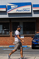 NORTH BERGEN, NJ - AUGUST 17: A man pass walk by the United States Postal Service office on August 17, 2020 in North Bergen New Jersey. Mail Delays Fuel Concern Trump Is Undercutting Postal System before elections , Mail-in voting across the country has led to a series of anomalous results in recent weeks (Photo by Kena Betancur/ VIEWpress via Getty Images)