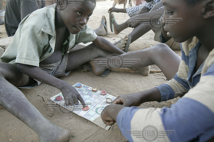 Beddington and his brother playing draughts on a home-made board using bottle tops as pieces. Many of the farming families here were forcibly moved from their old land which was flooded to create the Kariba dam Hydro Electric station. All the water from the dam is pumped 30km from the lake to the mining town of Maamba, leaving nothing for the nearby villages.