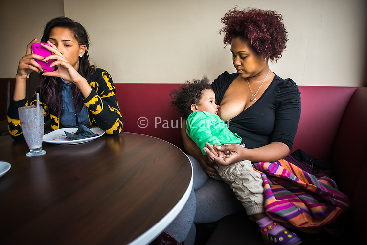 A mother  breastfeeds her 15 month old toddler in a sling in a cafe with her teenage daughter sitting next to her texting from her mobile phone.<br /> <br /> 18/10/12<br /> Harrow, England, UK
