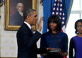 United States President Barack Obama (L) takes the oath of office from U.S. Supreme Court Chief Justice John Roberts as first lady Michelle Obama holds the bible and their daughter Malia looks on in the Blue Room of the White House in Washington, January 20, 2013.  .Credit: Larry Downing / Pool via CNP