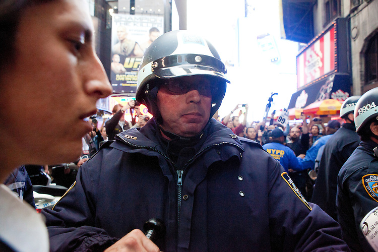 "Upon arriving at 46th Street and Broadway protesters with ""Occupy Wall Street"" are met by police barricades that prevent them from totally ""taking"" Times Square on October 15, 2011 in New York City.  While crowd estimates numbered in the tens of thousands, police tactics (including nets, motor scooters, barricades, arrests, and intimidation by riders on horseback) prevented the crowd, which had been split up, from joining together as one in the middle of Times Square."