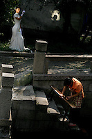 Women clean benches in a canal in Suzhou, China, while a bride-to-be has her portrait taken nearby.
