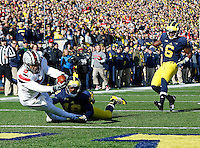 Ohio State Buckeyes quarterback Braxton Miller (5) falls into the end zone for a touchdown as he is tripped up by Michigan Wolverines defensive back Blake Countess (18) in the first quarter of the college football game between the Ohio State Buckeyes and the Michigan Wolverines at Michigan Stadium in Ann Arbor, MI Saturday afternoon, November 30, 2013. The Ohio State Buckeyes defeated the Michigan Wolverines 42 - 41. (The Columbus Dispatch / Eamon Queeney)