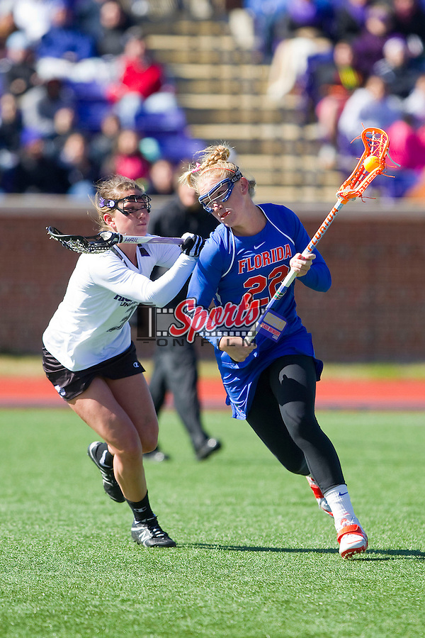 Brittany Dashiell (22) of the Florida Gators tries to avoid being checked by Alec Perry (3) of the High Point Panthers at Vert Track, Soccer & Lacrosse Stadium on February 17, 2013 in High Point, North Carolina.  The Gators defeated the Panthers 13-7.   (Brian Westerholt/Sports On Film)