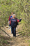 Senior woman wearing Ole Miss shirt from University of Mississippi leads other senior woman walking on path through William Faulkner Woods near Faulkner's home where he wrote in Oxford, Mississippi