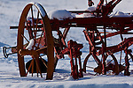 Steel rimmed farm implement from an era now past rests in the snow on an Iowa farm
