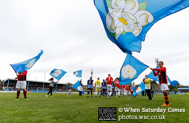 Players make their way past flag bearers onto the pitch. Yorkshire v Parishes of Jersey, CONIFA Heritage Cup, Ingfield Stadium, Ossett. Yorkshire's first competitive game. The Yorkshire International Football Association was formed in 2017 and accepted by CONIFA in 2018. Their first competative fixture saw them host Parishes of Jersey in the Heritage Cup at Ingfield stadium in Ossett. Yorkshire won 1-0 with a 93 minute goal in front of 521 people. Photo by Paul Thompson