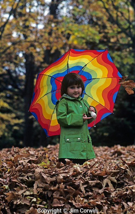 Young girl holding an umbrella with fall leaves Woodland Park, Seattle, Washington  USA