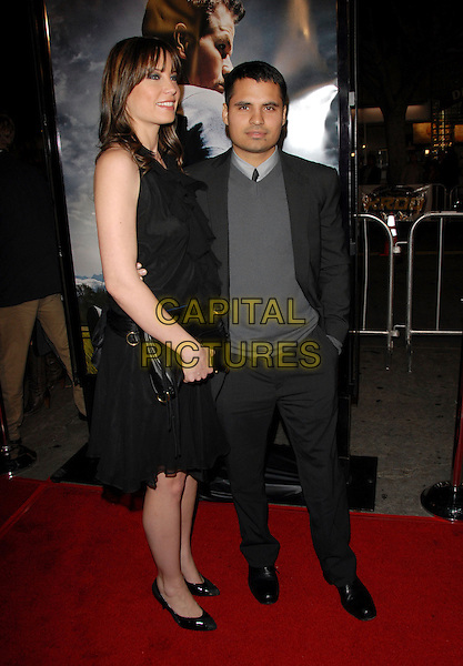 "MICHAEL PENA & GUEST.The Paramount Pictures L.A. Premiere of ""Shooter"" held at The Mann Village Theatre in Westwood, California, USA..March 8th, 2007.full length black suit dress grey gray sweater clutch purse .CAP/DVS.©Debbie VanStory/Capital Pictures"