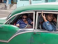 Three passengers in a taxi, Diez de Octubre, Habana