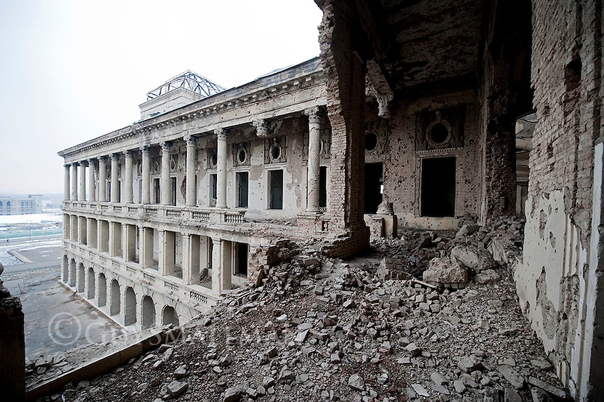 """Darul Aman Palace (""""abode of peace"""" or, in a double meaning """"abode of Aman[ullah]"""")[1] is a European-style palace, now ruined, located about sixteen kilometers (ten miles) outside of the center of Kabul, Afghanistan.Darul Aman Palace was built in the early 1920s as a part of the endeavours by King Amanullah Khan to modernize Afghanistan. It was to be part of the new capital city (also called Darul Aman or Darulaman) that the king was intending to build, connected to Kabul through a narrow-gauge railway. [2] The palace is an imposing neoclassical building on a hilltop overlooking a flat, dusty valley in the western part of the Afghan capital. Intended as the seat for a future parliament outside of Kabul, the building was unused for many years after religious conservatives forced Amanullah from power and halted his reforms. Darul Aman Palace was first gutted by fire in 1969. It was restored to house the Defence Ministry during the 1970s and 1980s. During the Communist coup of 1978, the building was set on fire. It was damaged again as rival Mujahideen factions fought for control of Kabul during the early 1990s. Heavy shelling by the Mujahideen after the end of the Soviet invasion left the building a gutted ruin."""