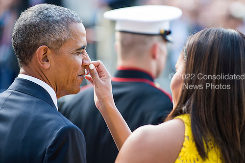 First Lady Michelle Obama primps United States President Barack Obama as they wait to welcome Prime Minister Lee Hsien Loong and Mrs. Lee Hsien Loong of Singapore to the White House with a ceremony on the South Lawn on August 2, 2016 in Washington, DC. The Official visit includes a State Dinner this evening. <br /> Credit: Pete Marovich / Pool via CNP