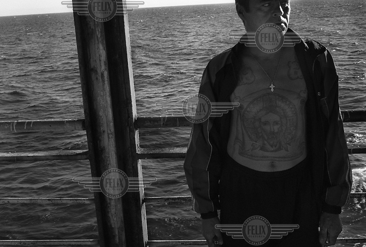 A man with a tattoo of Jesus Christ on his chest and stomach stands on board a ferry travelling from the mainland to Sakhalin island. .