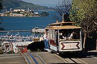 Cable car cresting hill and distant Alcatraz, San Francisco, California