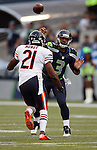 Seattle Seahawks' quarterback Russell Wilson (5) passes under pressure from Chicago Bears' safety Ryan Mundy (21) in a pre-season game at CenturyLink Field in Seattle, Washington on August 12, 2014.  Seattle beat Chicago 34-6. Wilson completed 15 of 20 passes for 202 yards passed for two touchdowns and ran for another in the win. © 2014.  Jim Bryant Photo. ALL RIGHTS RESERVED.