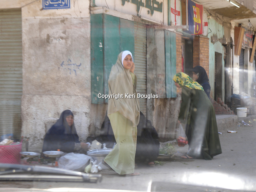 Giza area, veiled young women at small corner market.