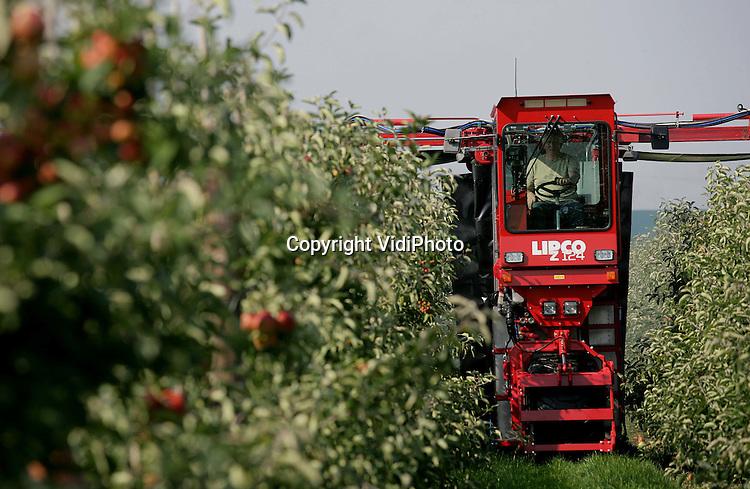 Foto: VidiPhoto..ANDELST - Fruitteler Jan van Olst uit Andelst heeft een primeur. De Betuwse fruitteler bezit de enige zelfrijdende tunnelspuit van Europa. De spuit is gloednieuw en wordt op dit moment gebruikt om de appels te spuiten tegen bewaarrot. De zelfrijdende tunnelspuit werkt als een soort wasstraat en wordt niet meer getrokken door een tractor. De investering kost 125.000 euro, maar er wordt per jaar tussen de 15.000 en 20.000 euro aan spuitmiddelen bespaard, naast arbeidsbesparing en milieuvoordeel.