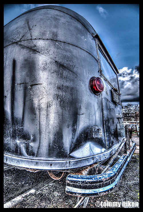 Old Airstream trailer atop parking garage, used as a tool shed for a pea-patch garden project